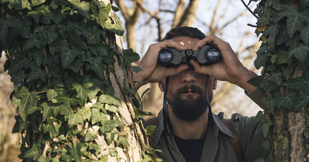 Man in the forest looks through binoculars